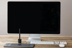 Bildschirm und Tastatur und Maus auf einer hölzernen Tabelle mit Whit Lizenzfreie Stockbilder