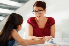 Bildung mit der Mutter-helfenden Tochter, die zu Hause Schulhausarbeit tut lizenzfreies stockfoto