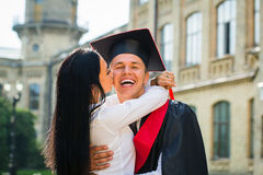 Bildung, Staffelung und Leutekonzept - Gruppe lächelnde Studenten in den Doktorhuten und in den Kleidern draußen stockbild