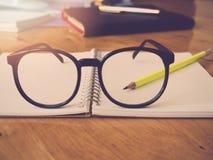Bildung und Bürokonzept Bleistiftnotizbuch und -brillen Stockbilder