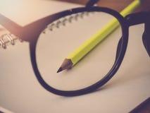 Bildung und Bürokonzept Bleistiftnotizbuch und -brillen Lizenzfreie Stockfotos