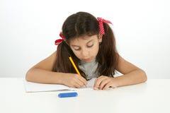 Bildung und Schulkonzept Schreiben des kleinen Mädchens Lizenzfreie Stockfotografie