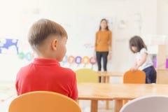 Bildung, Volksschule, Lernen und Leutekonzept - Gruppe der Schule scherzt mit dem Lehrer, der im Klassenzimmer sitzt stockfotografie