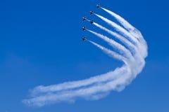 Bildung von Düsenflugzeugn dreht sich im Team in blauen Himmel Stockfotos