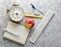Bildungsausrüstung Wecker, Notizblock, Machthaber, Apfel, Stift, Kompassse auf einem grauen konkreten Hintergrund Draufsicht, fla stockbild