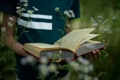 Bildungskonzept - Jugendlicher hält ein Buch in seinen Händen in der Natur lizenzfreie stockfotos