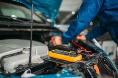 Bilelektrikeren kontrollerar batteriniv?n arkivfoto