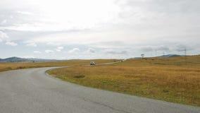 Bilen är vita Niva ritter längs asfaltvägen i bergen och vändna stock video