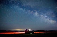 Bilen av turisten mot stjärnahimlen Arkivfoto