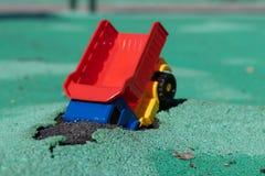 Bilen avverkar in i gropen Hade den plast- lastbilen för leksaken med en röd kropp en olycka Hål på Asphalt Coating Olyckan h royaltyfri bild