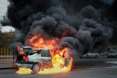 Bilen bränner med flamman och rök Arkivbilder