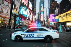 Bilen för NYPD-polistruppen går till den nöd- appellen med larm- och sirenljus i de Time Square gatorna av New York City, New Yor Royaltyfri Bild