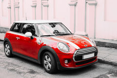 Bilen för röd färg med vit gör randig Mini Cooper Parked On Street in royaltyfri bild