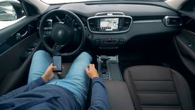 Bilen flyttar sig automatiskt, medan chauffören bläddrar hans telefon Futuristisk automatiserad bilparkering lager videofilmer
