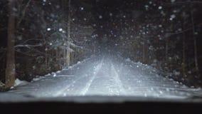Bilen fortskrider skogen snö-täckt väg arkivfilmer