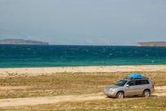 Bilen går på den sandiga kusten av Lake Baikal på den Olkhon ön royaltyfria bilder
