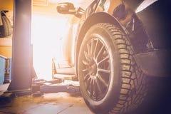 Bilen i garage av service för den auto reparationen shoppar med special reparera utrustning royaltyfri bild