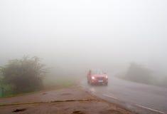 Bilen i tät dimma arkivfoto