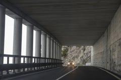 Bilen kör i en tunnel i bergen Arkivbilder