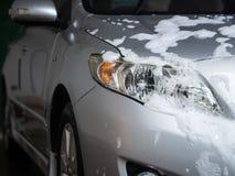 Bilen med vit tvål på kroppen i bilomsorg shoppar Biltvätt c arkivfoton