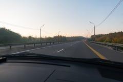 Bilen på den tomma vägen Fotografering för Bildbyråer