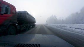 Bilen rider på vägen bland träden som täckas med snö, tjock dimma arkivfilmer