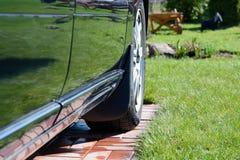 Bilen rullar in gården av en bakgrund för landshus Royaltyfri Bild