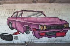 Bilen without rullar in reparationen: grafitti på väggen arkivbild