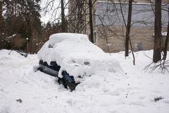 Bilen som täckas med det tjocka lagret av snö, i gården av det bostads- huset i provilcial stad royaltyfria bilder