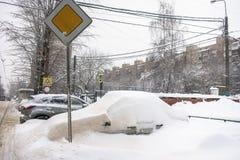 Bilen som täckas med det tjocka lagret av snö, i gården av det bostads- huset i provilcial stad fotografering för bildbyråer