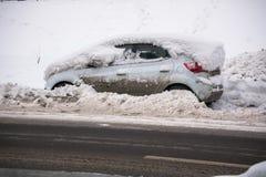 Bilen som täckas med det tjocka lagret av snö och gyttja, på körbanan arkivfoton