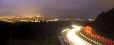 Bilen tänder på natten på vägen som går till staden Arkivfoton