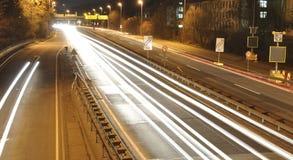 Bilen tänder på tysk huvudvägkonstruktionsplats med tecken på natten, långt exponeringsfoto av trafik Fotografering för Bildbyråer