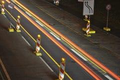 Bilen tänder på tysk huvudvägkonstruktionsplats med tecken på natten, långt exponeringsfoto av trafik Royaltyfri Foto