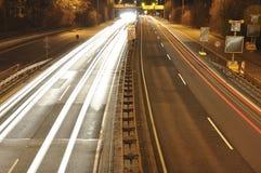 Bilen tänder på tysk huvudvägkonstruktionsplats med tecken på natten, långt exponeringsfoto av trafik Arkivfoton