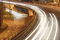 Bilen tänder på tysk huvudvägkonstruktionsplats med tecken på natten, långt exponeringsfoto av trafik Royaltyfri Bild