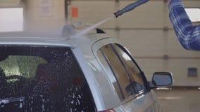 Bilen tvättas med högtrycks- vatten på biltvätt stock video