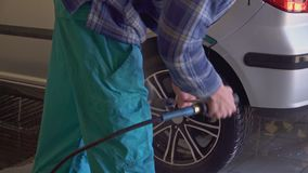 Bilen tvättas med högtrycks- vatten på ett biltvättslut upp arkivfilmer