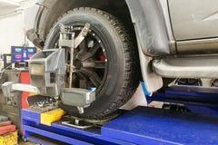 Bilen 4WD genomgår hjulet arrangera i rak linje i garage Arkivfoto