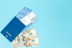 Bilety dla samolotu i paszporta, dolary z modelem samolot na błękitnym tle Odbitkowa przestrzeń dla teksta zdjęcia stock