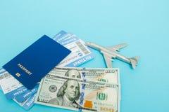Bilety dla samolotu i paszporta, dolary z modelem samolot na b??kitnym tle Odbitkowa przestrze? dla teksta fotografia stock