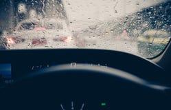 Bilfönstret för sikten med regn tappar från inre på exponeringsglas eller vindrutan, suddig trafik på regnig dag i staden royaltyfria foton