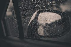 Bilfönstret med regn tappar på exponeringsglas eller vindrutan royaltyfri bild