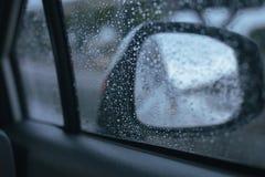 Bilfönstret med regn tappar på exponeringsglas eller vindrutan, suddig trafik på regnig dag arkivfoto