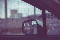 Bilfönstret med regn tappar på exponeringsglas eller vindrutan, suddig trafik på regnig dag i staden royaltyfria foton