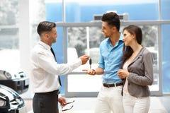Bilförsäljare Giving en tangent från den nya bilen till de unga ägarna Arkivbild