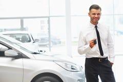 Bilförsäljare Giving Key av den nya bilen på visningslokalen arkivbild