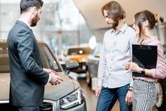 Bilförsäljare med unga par i visningslokalen arkivfoto