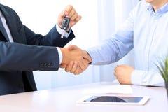 Bilförsäljare som räcker över tangenterna för en ny bil till en ung affärsman affärshandskakningfolk två Arkivbilder