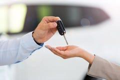 Bilförsäljare som räcker biltangenter till kvinnan royaltyfri bild